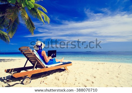 young woman with laptop on tropical beach - stock photo