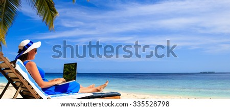 young woman with laptop on tropical beach vacation, panorama ideal for banners - stock photo
