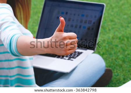 Young woman with laptop sitting on green grass