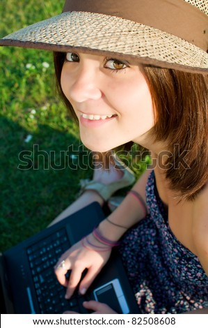 Young woman with laptop sitting on green grass and looking up - stock photo
