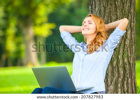 Young woman with laptop sitting on green grass in the park and relaxing