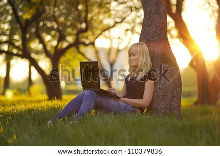 Young woman with laptop sitting on green grass in the park at sunset