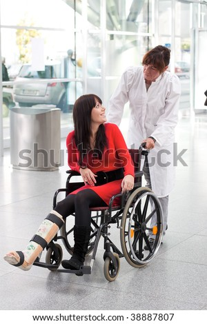 Young woman with leg in plaster, wheelchair and nurse