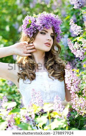 Young woman with lilac wreath. Woman with lilac flowers in springtime. - stock photo