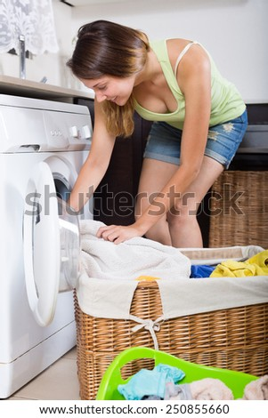 Young woman with linen basket in  kitchen