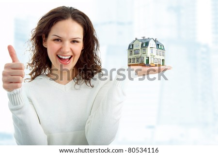 young woman with little house in hand on white