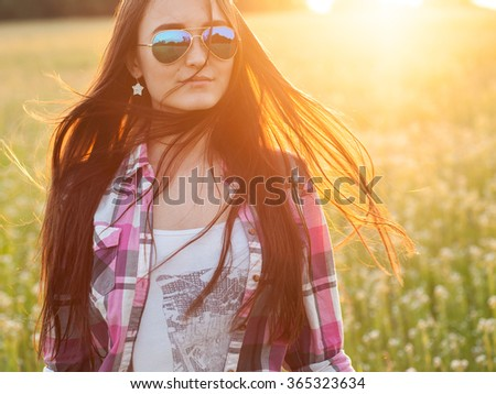 Young woman with long beautiful hair standing under an rays of sunset - stock photo