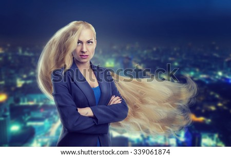 Young woman with long blond hair against night city background - stock photo