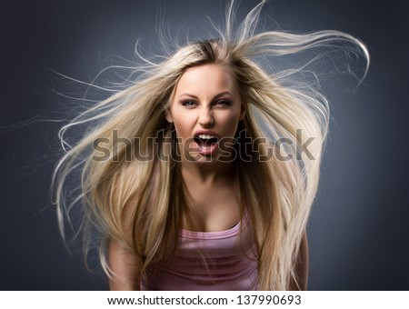 young  woman with long blond hair screaming on dark-grey background
