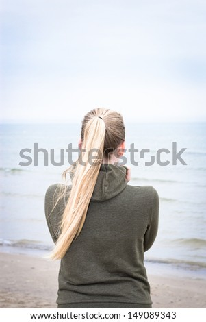 Young woman with long blond ponytail on a foggy morning on the beach