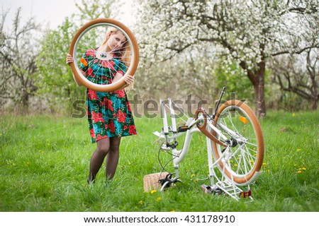 Young woman with long blonde hair in flowered dress standing next to white retro bicycle upside down and holding in hand a wheel that is removed from bike on the green grass - stock photo