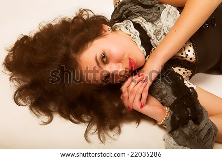 Young woman with long brown  curly hair and green  eyes laying on floor.