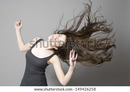 Young woman with long brown wavy hair dancing against gray background - stock photo