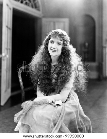 Young woman with long Curls, Curly Hair, Curly sitting on a chair and smiling - stock photo