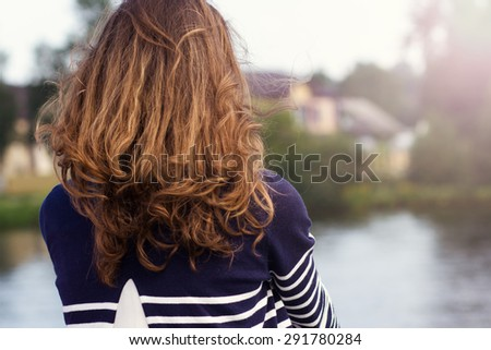 Young woman with long curly hair standing with her back looking at the water scenery. - stock photo