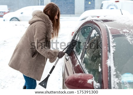 Young woman with long hair cleaning car after blizzard - stock photo