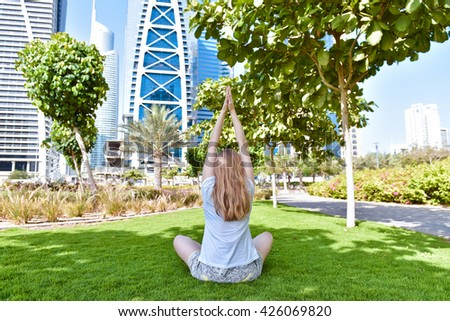 Young woman with long  hair relaxing and do yoga exercises on the grass in Dubai. Hot summer day with blue sky, skyscraper buildings and trees
