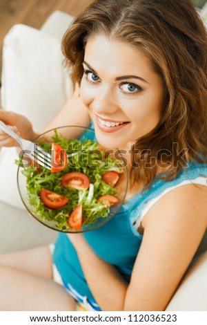 Young woman with long hair sitting  on sofa at home and eating healthy food.
