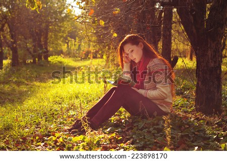 Young woman with long red hair reading under the tree in autumn forest - stock photo