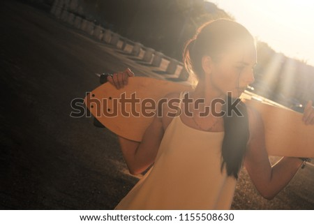 Young Woman with longboard behind her neck backlit by bright summer sun