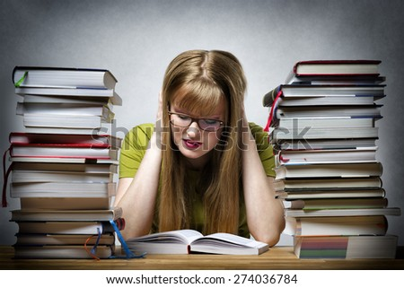 young woman with lots of books at a table is reading bored book - stock photo