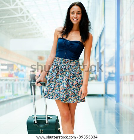 Young woman with luggage at the international airport. She is very happy of her vacation at warm country on christmas holidays - stock photo