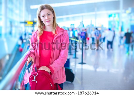 Young woman with luggage in airport. - stock photo