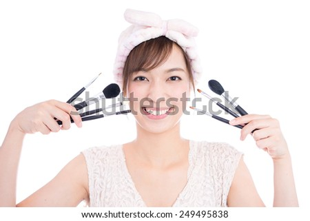 young woman with makeup brush, isolated on white background - stock photo