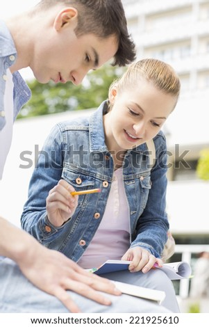 Young woman with male friend studying together at college campus - stock photo