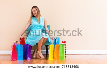 Young woman with many brightly colored shopping bags indoors