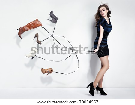 Young woman with many shoes - stock photo