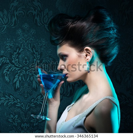 Young woman with martini glass in blue light on damask wallpaper background  - stock photo