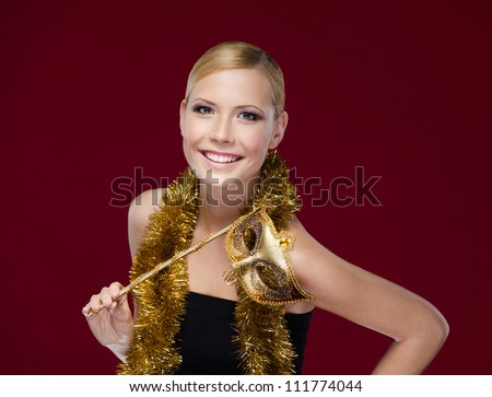 Young woman with masquerade mask and tinsel, isolated on purple - stock photo