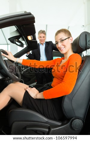 Young woman with mature man sits in car on driver seat with her hand on the steering wheel in a car dealership, obviously she is buying or selling the convertible - stock photo