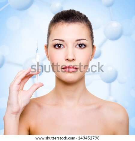 Young woman with medical syringe face over molecule background - stock photo