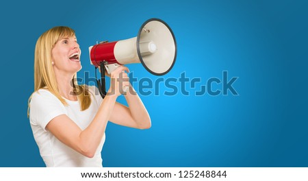 Young Woman With Megaphone against a blue background - stock photo