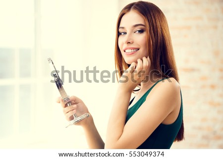 Young woman with mirror, indoors. Beautiful caucasian model in make up and beauty treatment concept shoot.