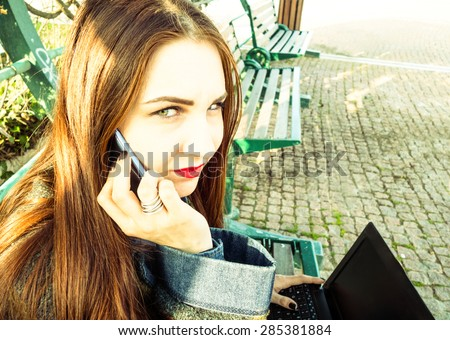 Young woman with mobile and laptop sitting in a park calling for help after being harassed - Green eyes model with angry expression - Concept of sadness and solitude caused by violence against women - stock photo