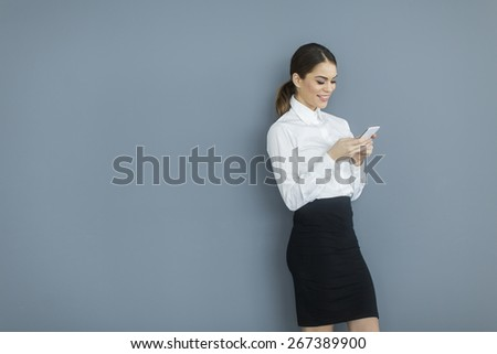 Young woman with mobile phone by the wall - stock photo