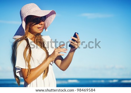 young woman with mobile phone on a beach, bali - stock photo