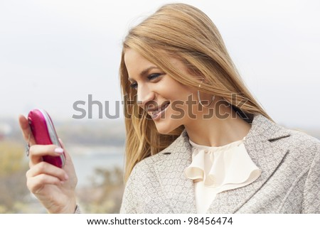 Young Woman with mobile phone walking background is blurred city - stock photo