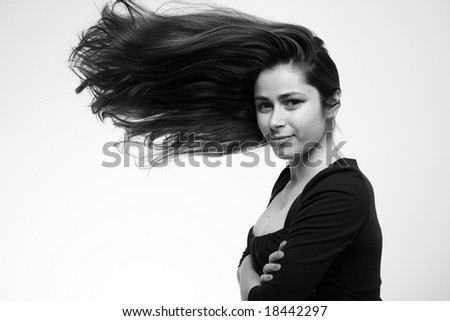 Young woman with moving hair in studio