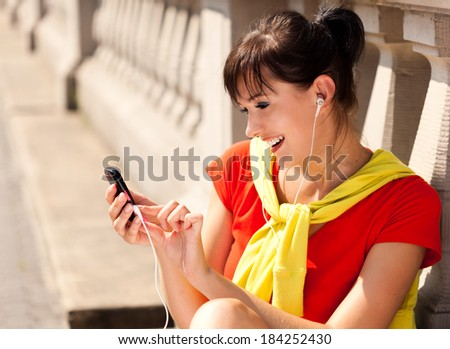 Young woman with mp3 player, smiling, outside - stock photo