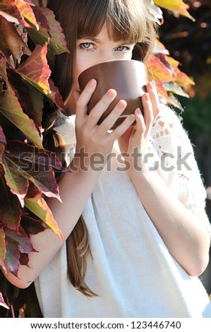 young woman with mug of hot drink outdoors - stock photo