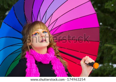 Young woman with multicolor umbrella at forest