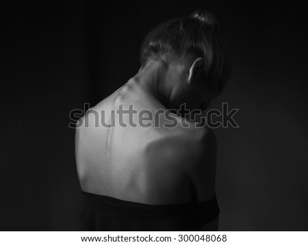 young woman with naked back over black background. sad girl - stock photo