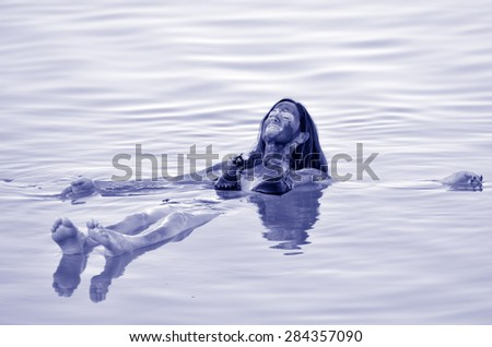 Young woman with natural mineral mud on her body floating on the Dead Sea, Israel - stock photo
