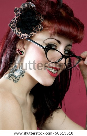 young woman with neck tattoo and funky glasses - stock photo
