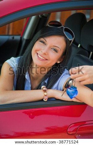 Young woman with new car and car keys