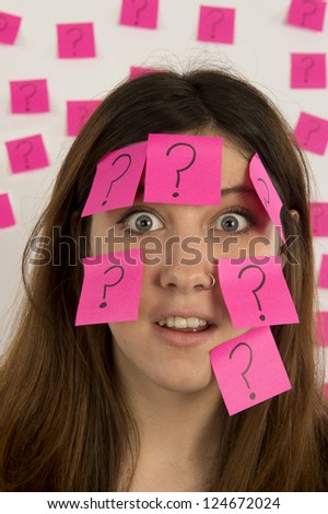 Young woman  with nose ring  with pink sticky notes and question mark thinking about decision making - stock photo